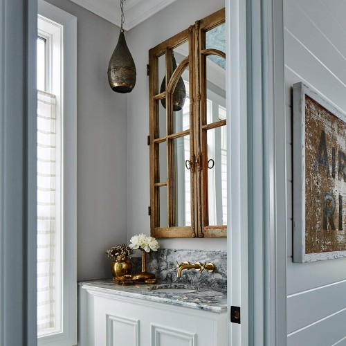 Entrance to powder room, white walls with striking marble countertop and brass accents