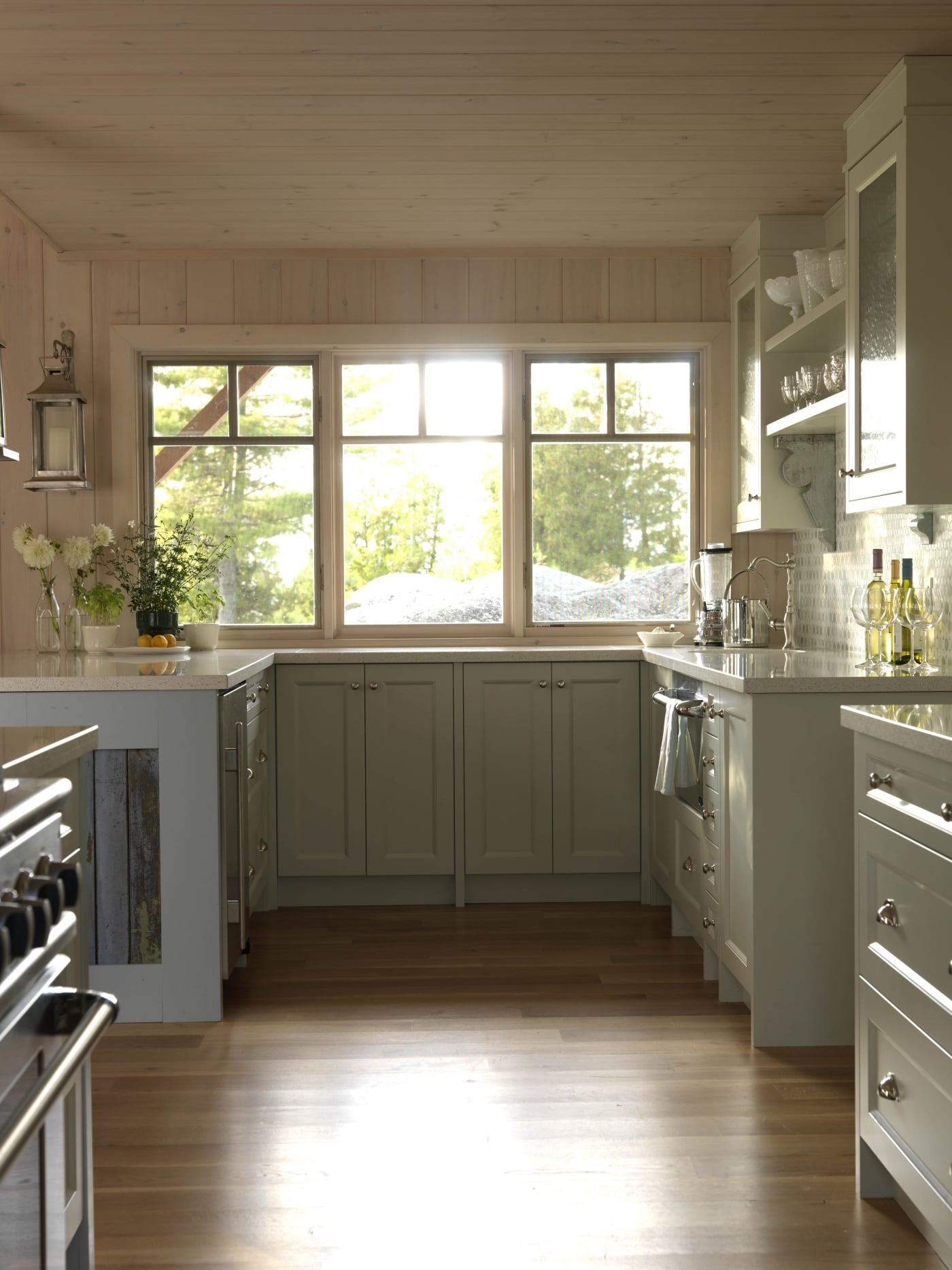 Painted cabinets, whitewashed knotty pine paneling, and bright sunlight in cottage kitchen