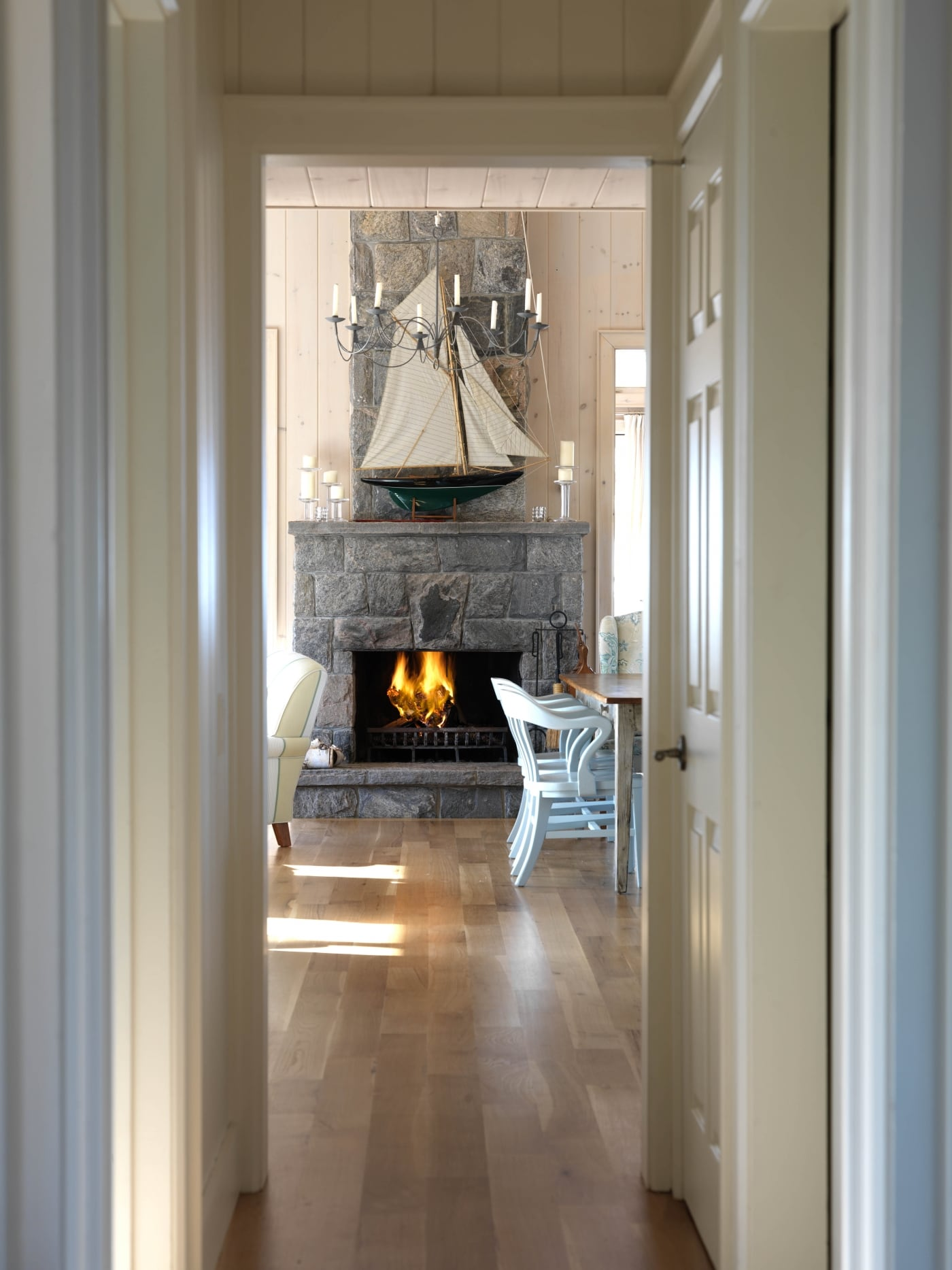 Down the hall view of fireplace in cottage by Sarah Richardson