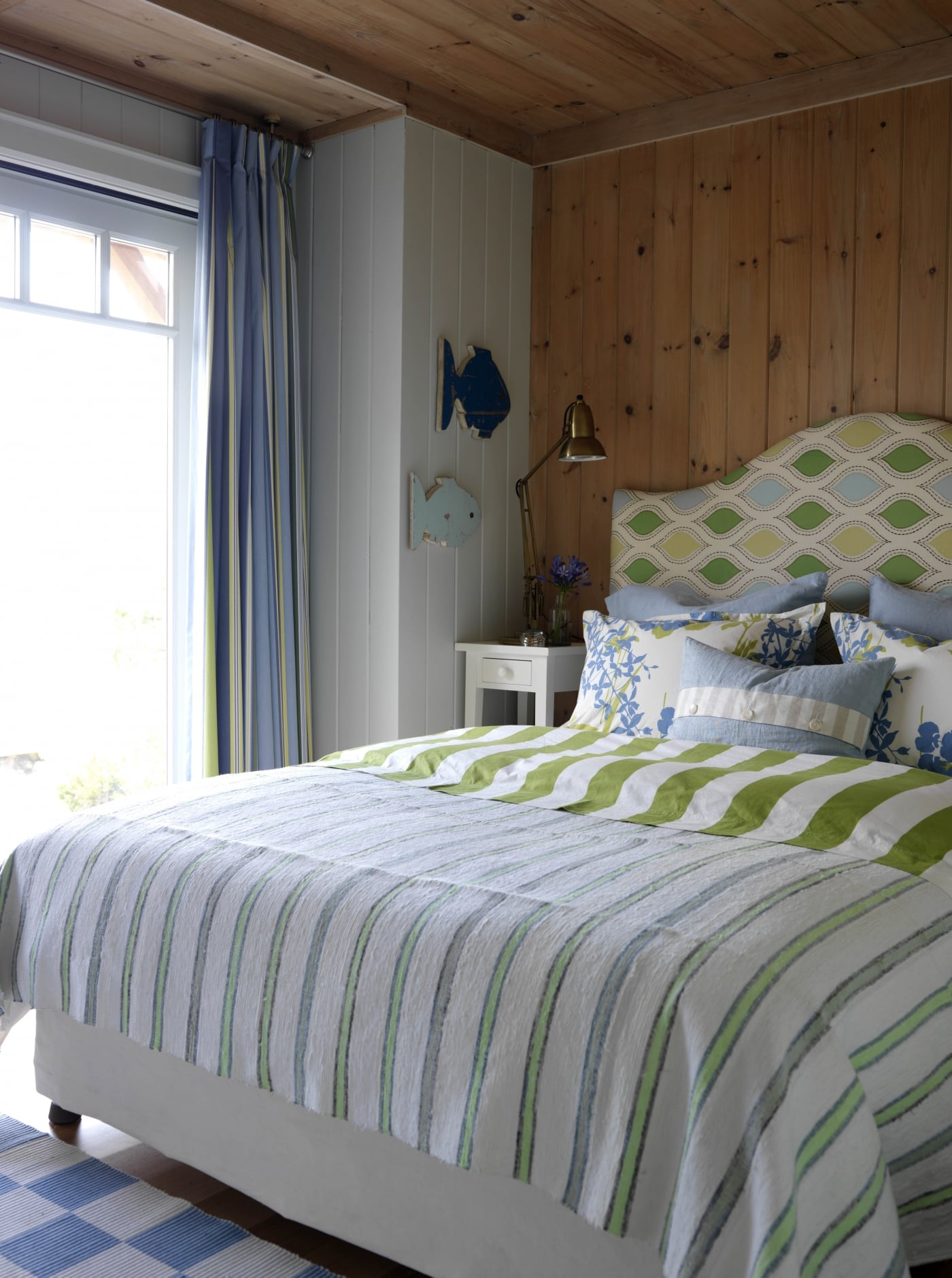 Bed with green headboard beside a window with knotty pine paneling. #SarahRichardson #cottagestyle