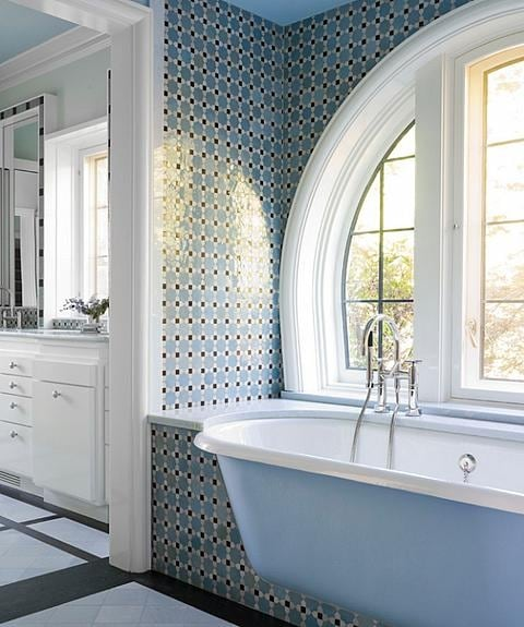 Blue clawfoot tub and beautiful tiled wall with arch window by Sarah Richardson
