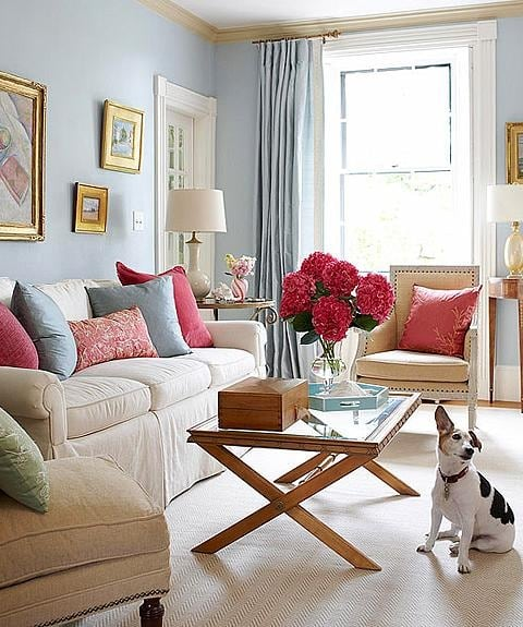 Blue walls and bright pink accent colors in this living room design by Sarah Richardson