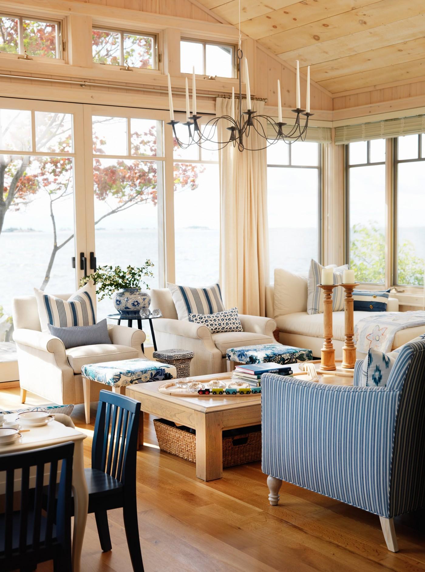 Blue seating area against large windows overlooking water - Sarah Richardson