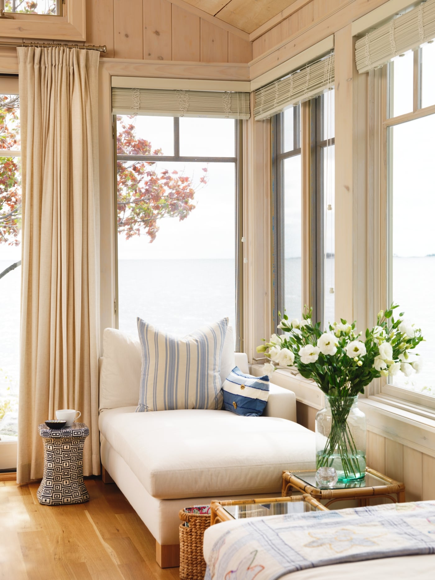 White sofa lounge in bright corner of sun room with knotty pine paneling