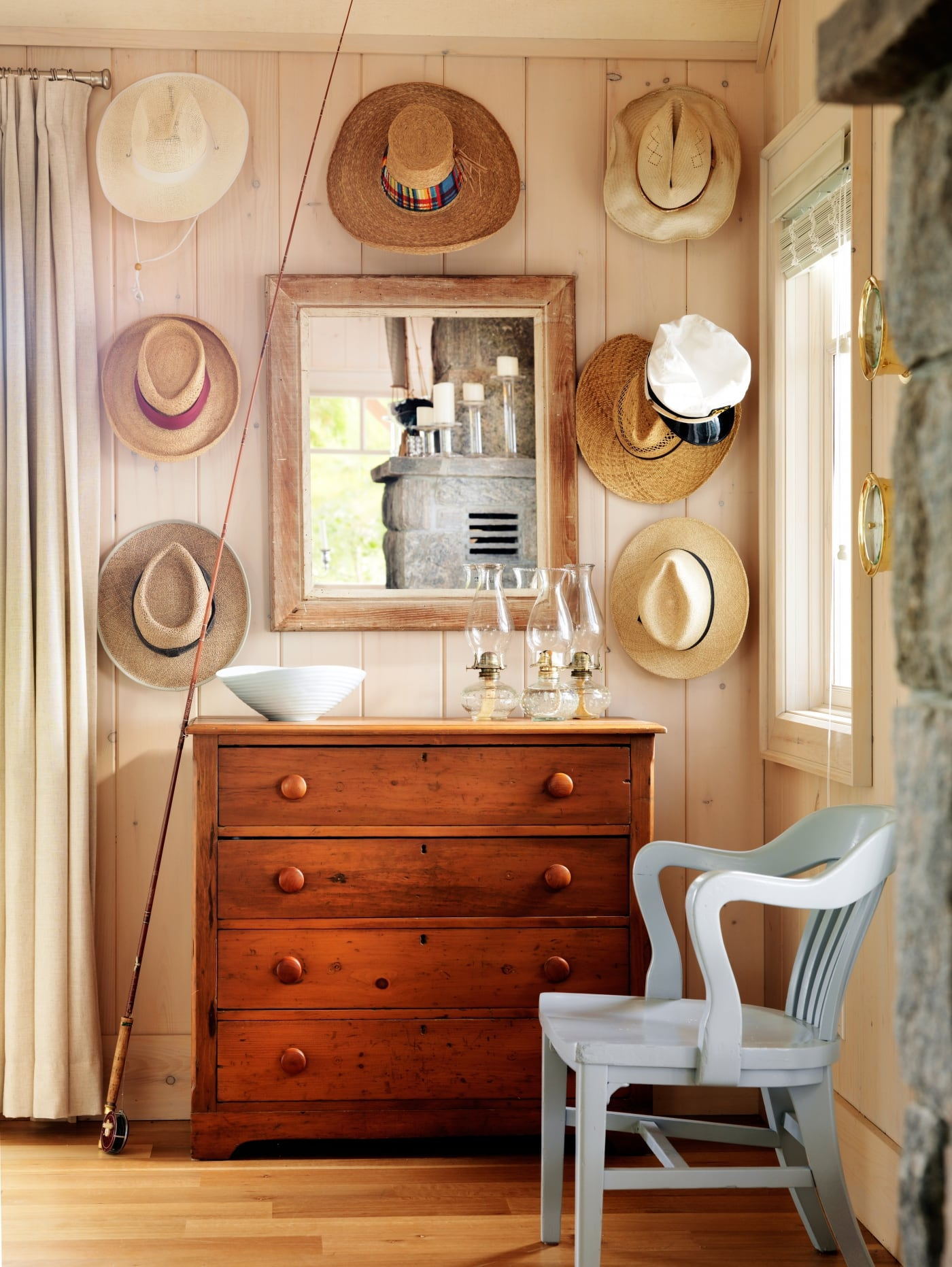 Storage unit placed by the front door and hats hung on wood paneled wall. #SarahRichardson #cottagestyle