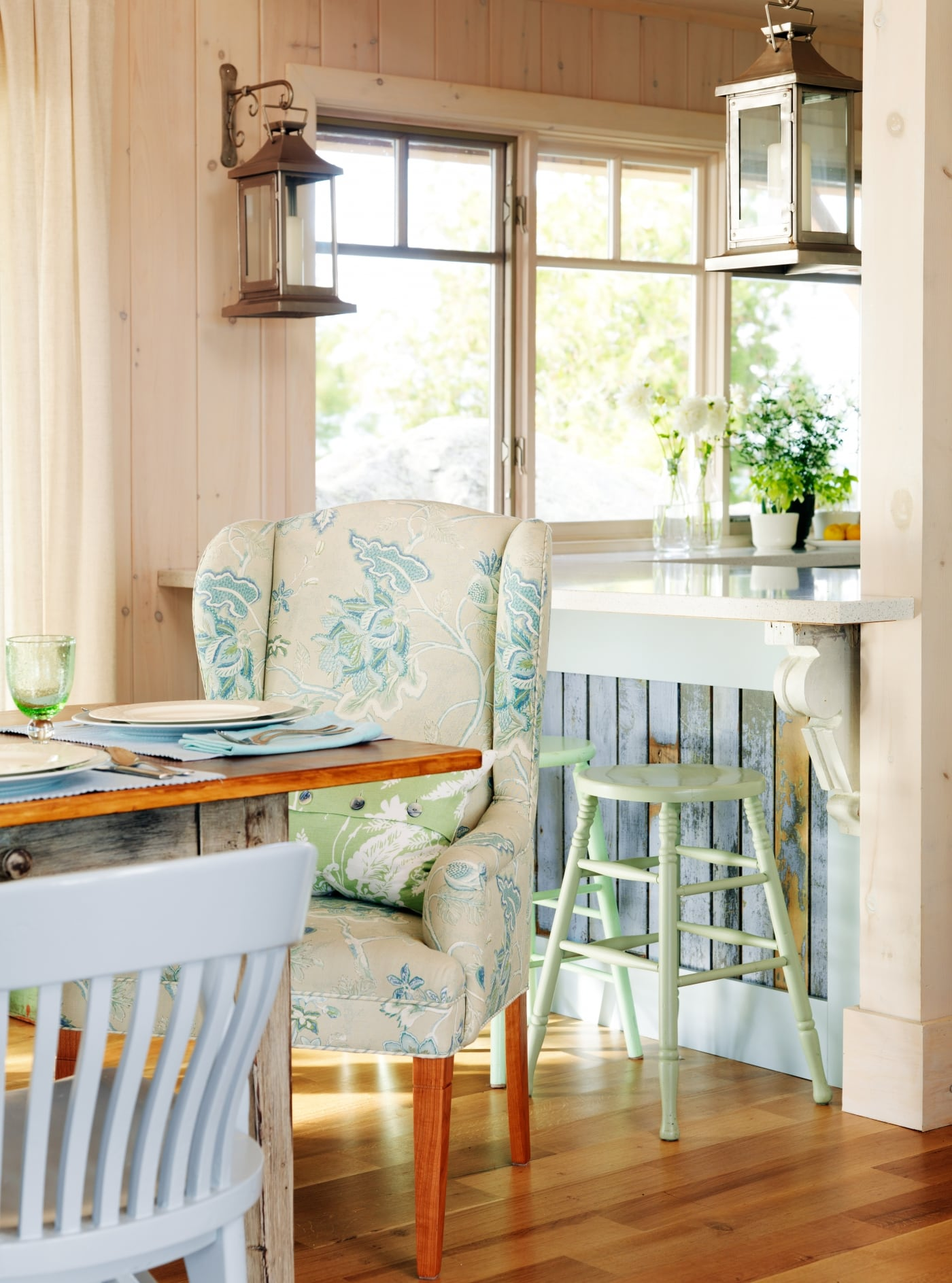 Floral patterned wing back chair and rustic planked breakfast bar with weathered stools