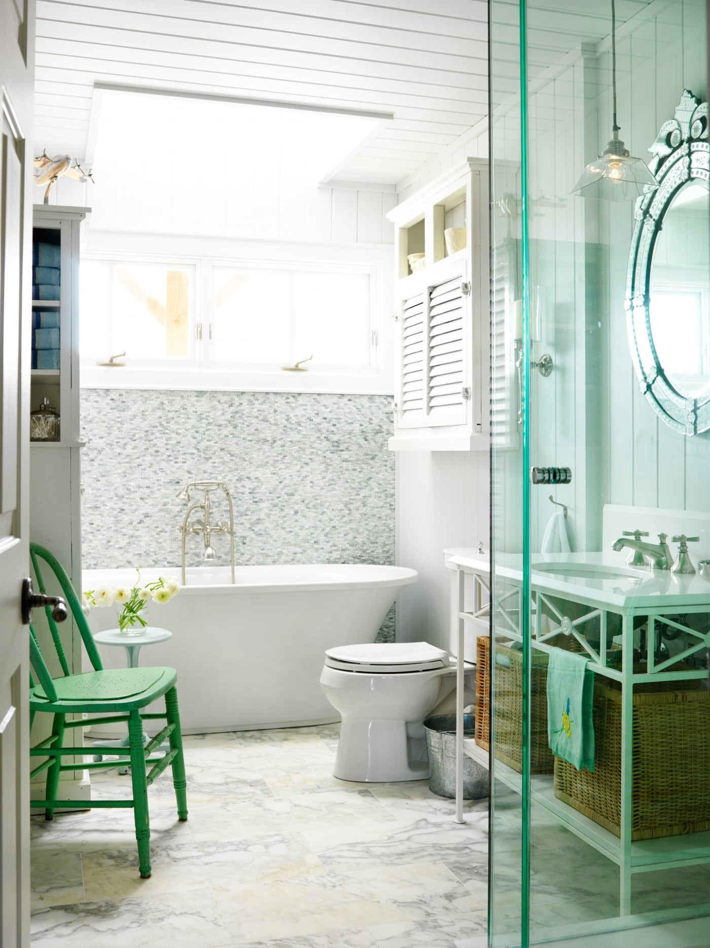 Country bathroom with freestanding tub, vintage chair, and Venetian mirror. #SarahRichardson #cottagestyle