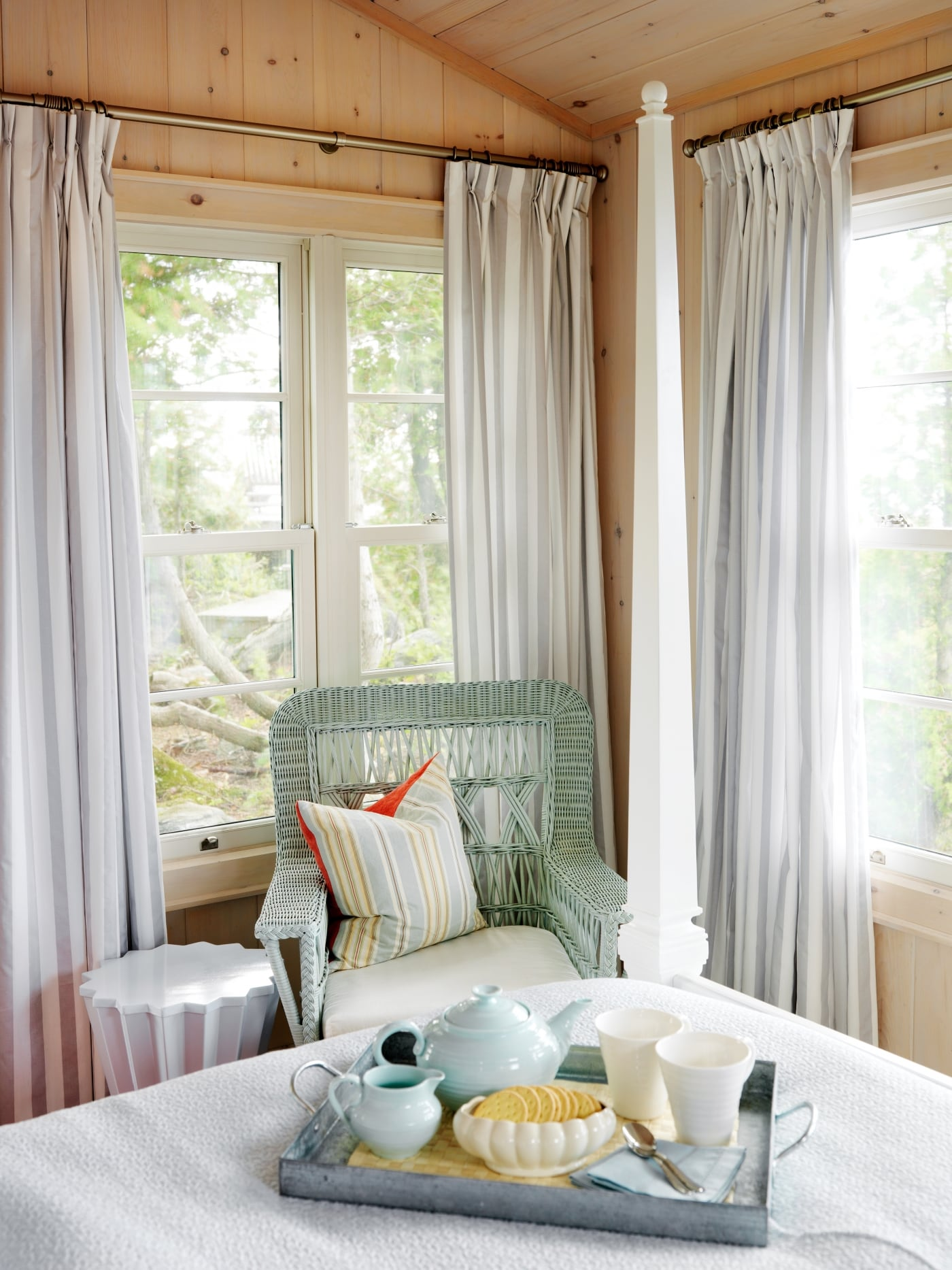 #SarahRichardson #cottagestyle Knotty pine paneling in cottage bedroom with green wicker chair - Sarah Richardson