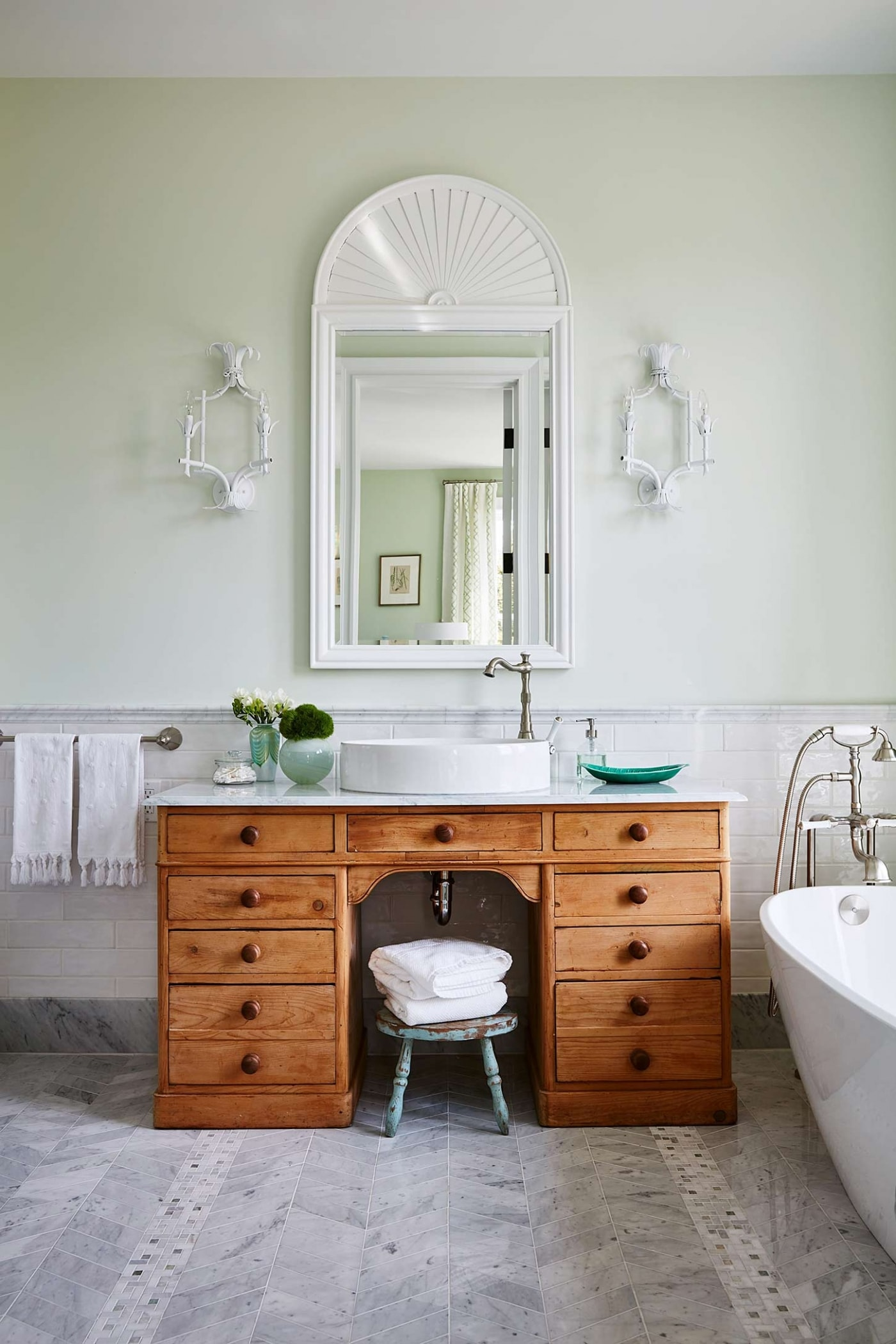 Wooden vanity, with mirror hung on wall in bathroom with marble floor, freestanding tub, and subway wainscot