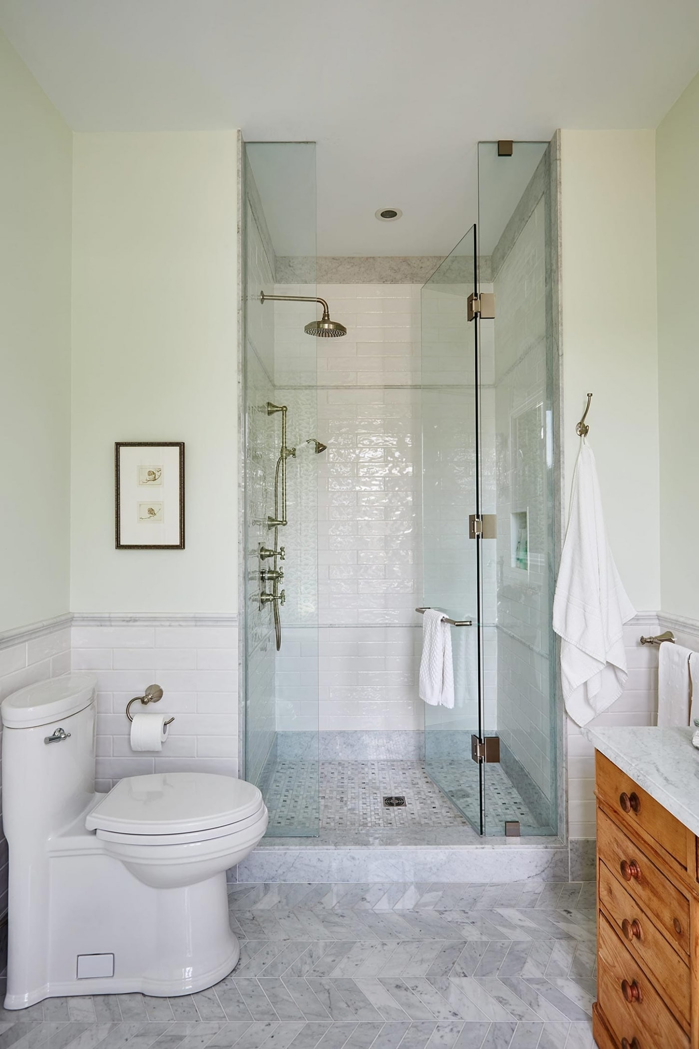 White subway tile and glass Standup Shower in elegant marble bathroom by Sarah Richardson