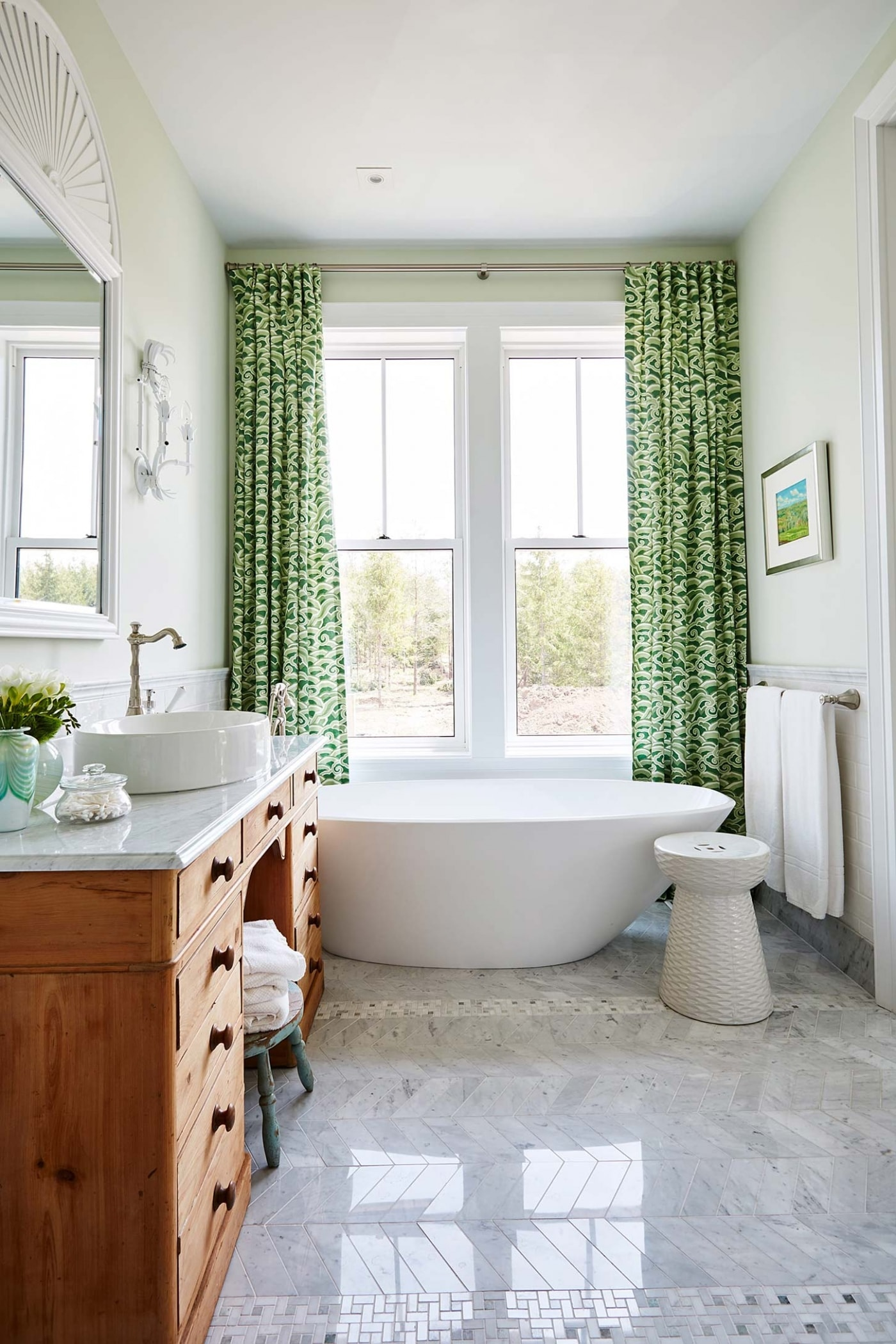 Gorgeous green bathroom with window, vintage wood vanity, and green patterned curtains - design by Sarah Richardson