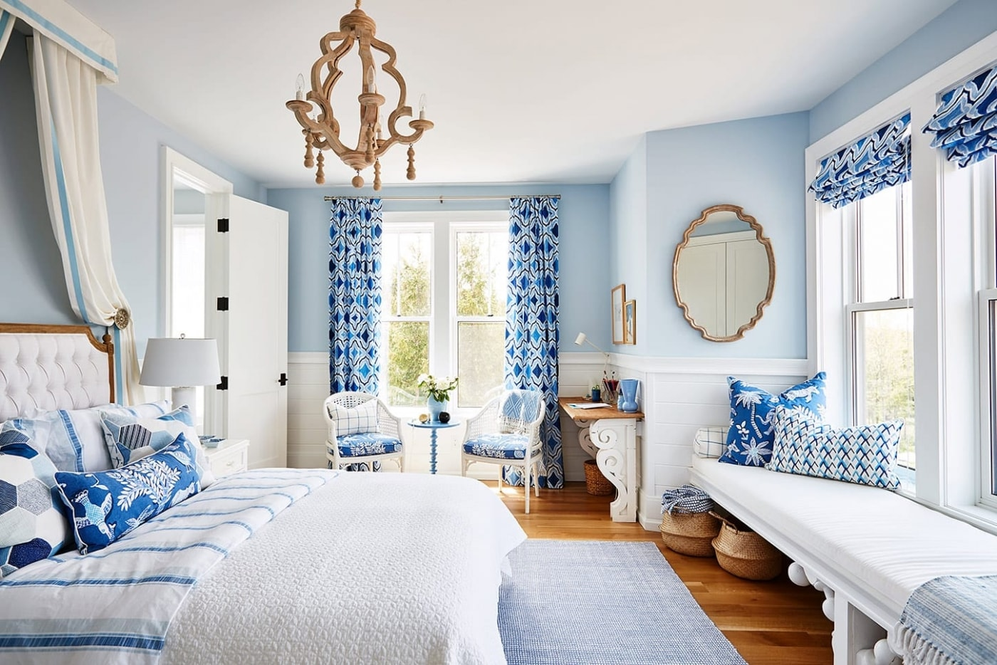 Blue and white girls room with window seat, canopy, and wood chandelier