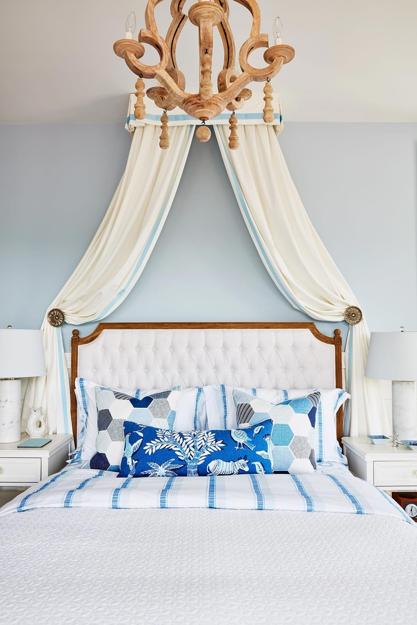 Romantic canopy over upholstered bed in blue bedroom - Sarah Richardson
