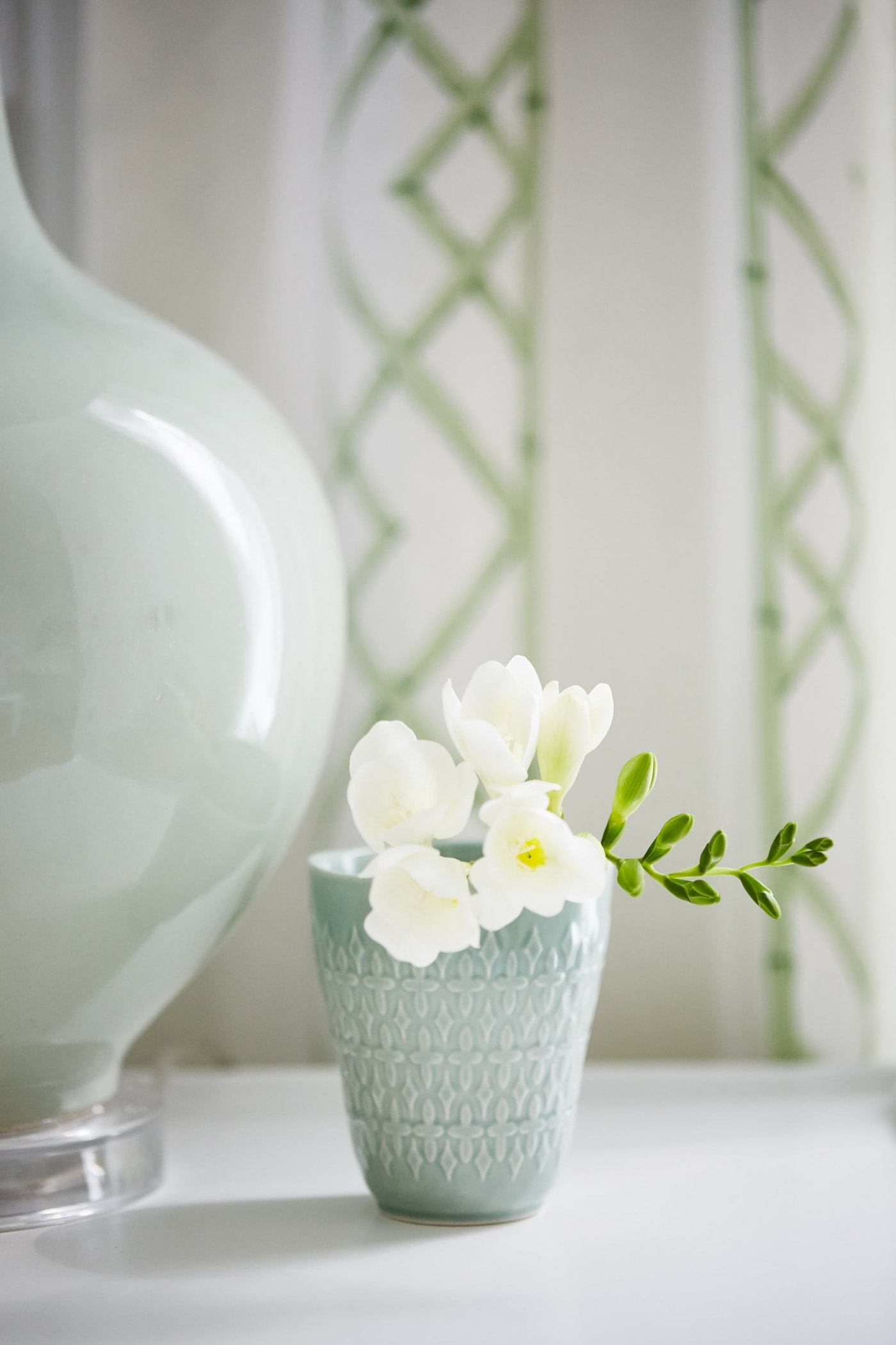 Beautiful aqua blue vase with white flowers and mint green lamp