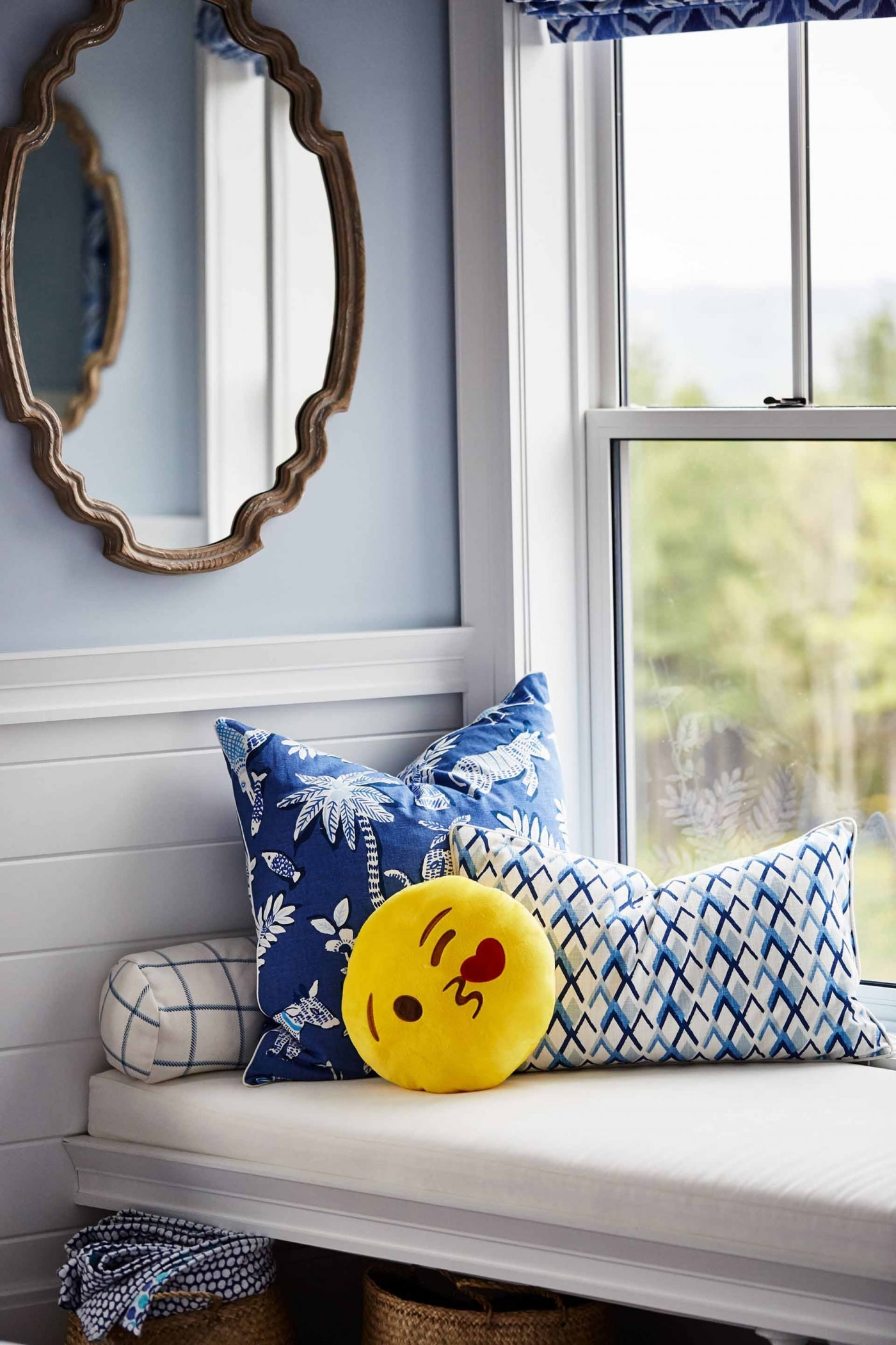 Sweet emoji pillow and blue print pillows on window seat in blue girl's room