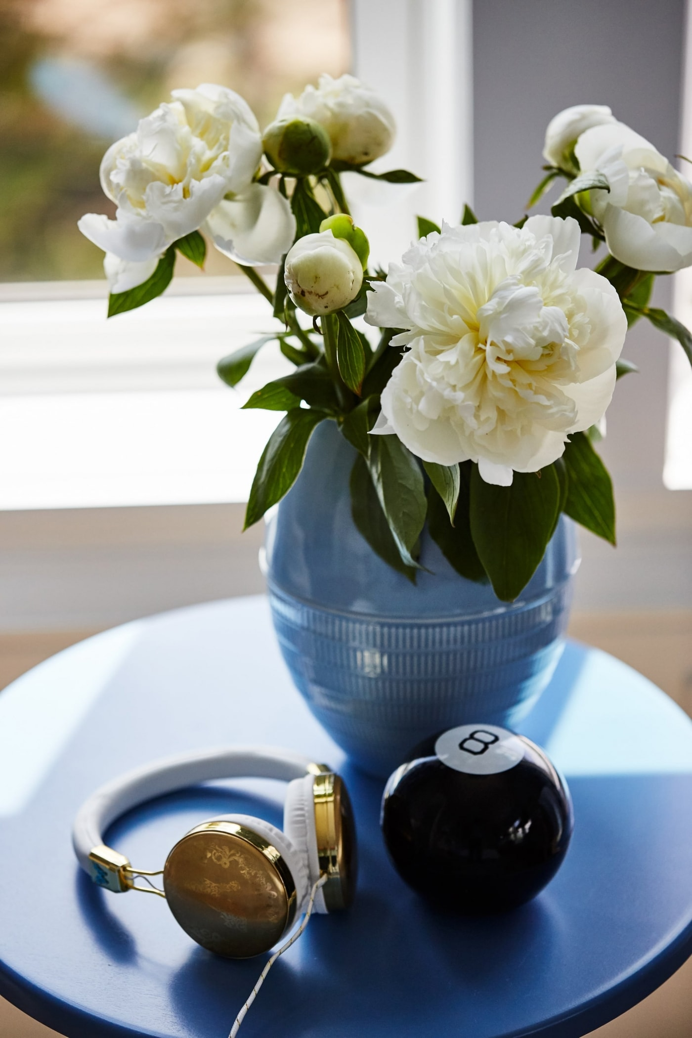 Royal blue vase with flowers on blue round table with magic 8 ball and headphones