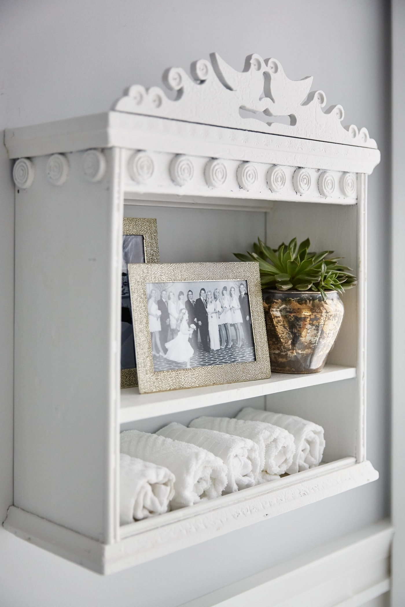 Vintage white shelves with ornamental detail to hold accessories in bathroom