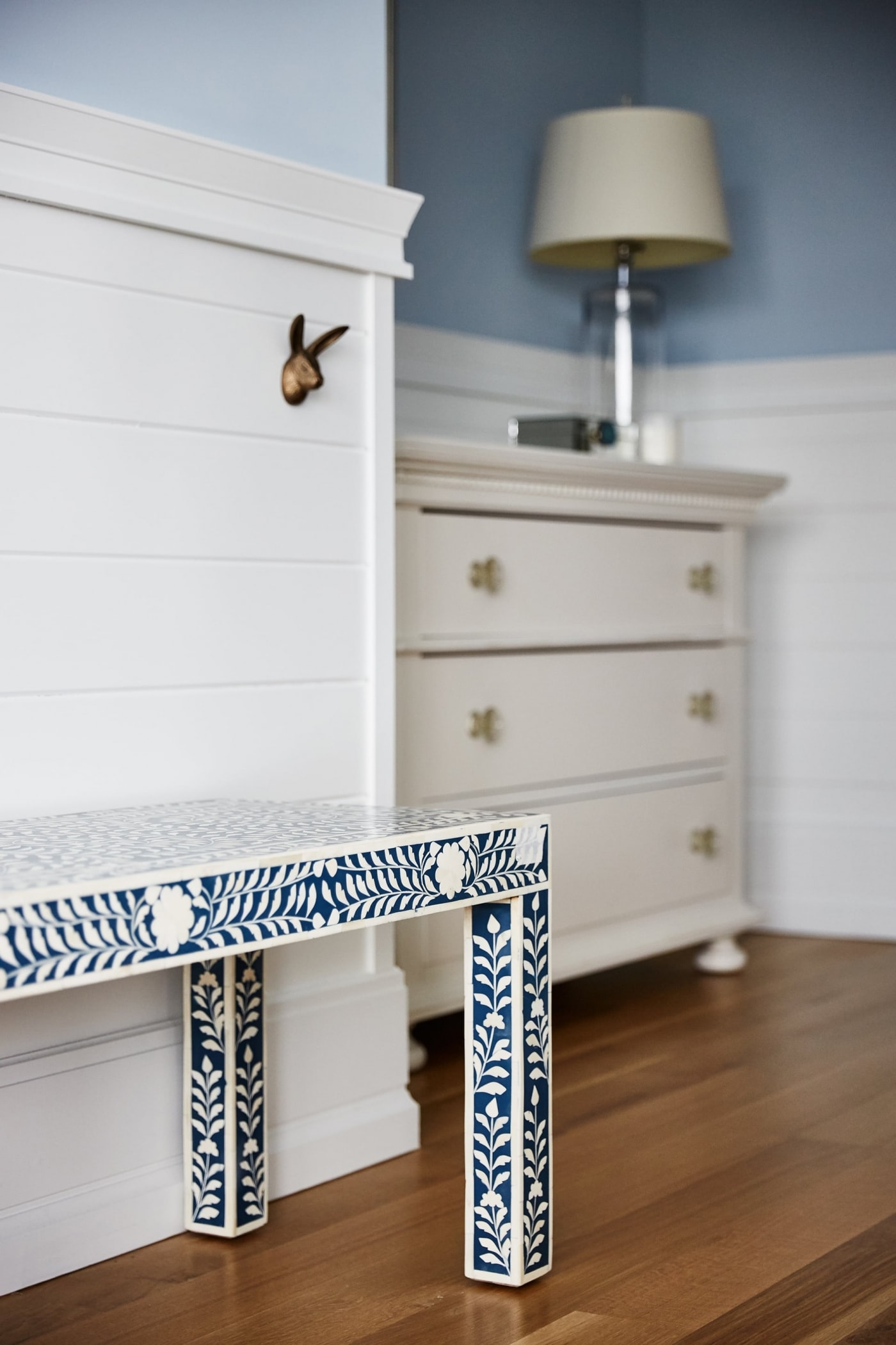 Brass bunny hooks on wainscot wall with blue bench in girl's room - Sarah Richardson