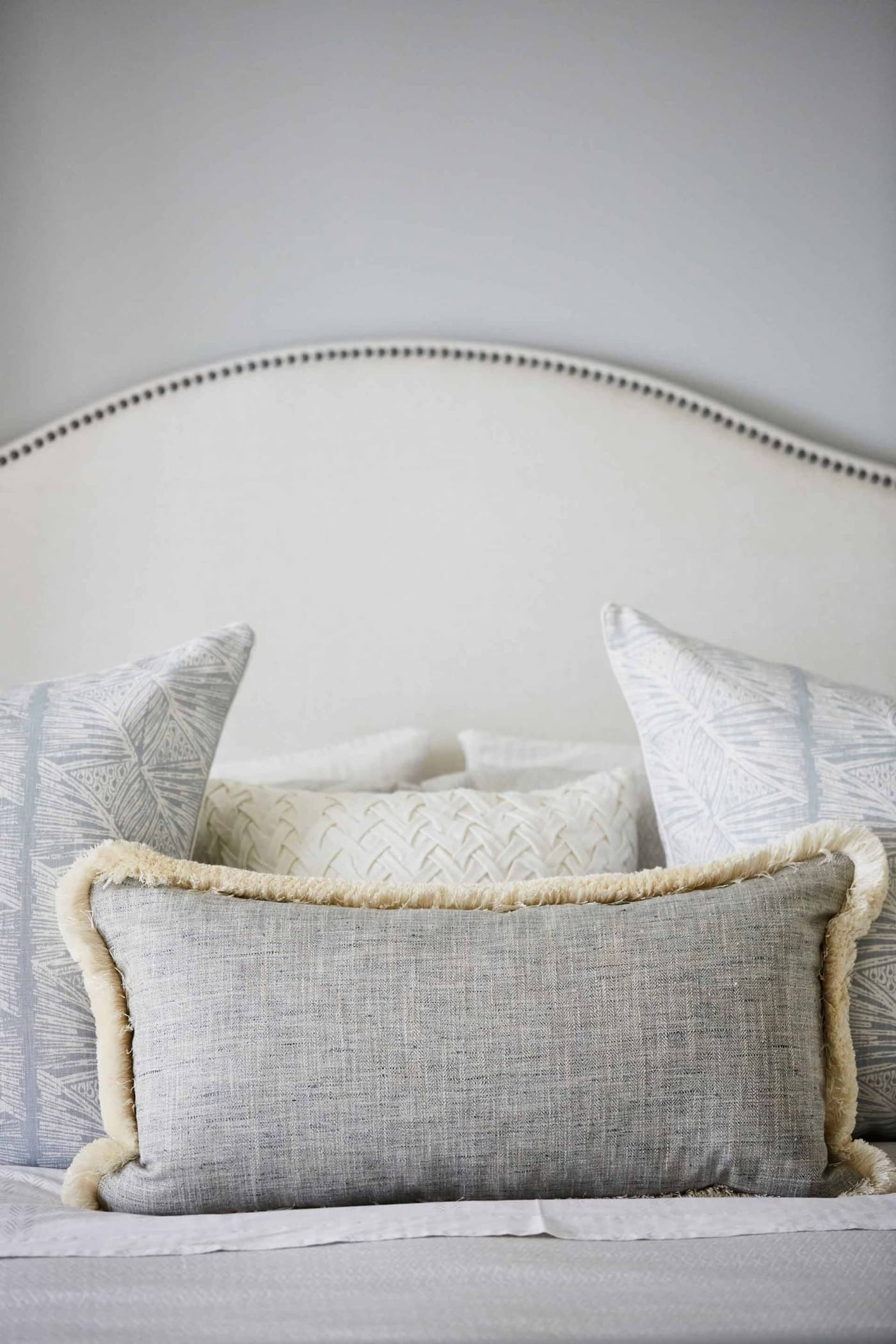 Master Bedroom with upholstered headboard, nailhead trim, light blue grey linens - Sarah off the Grid