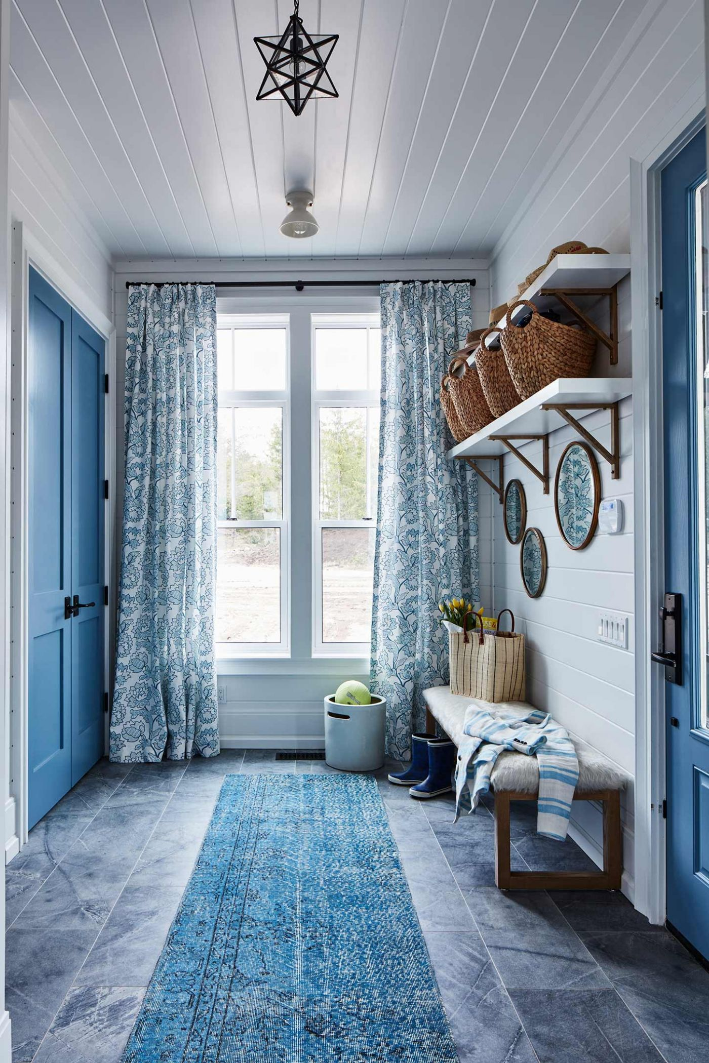 Mudroom - Sarah off the Grid. Blue stone tiles, a blue runner, and beautiful blue curtains in a mud room with open shelving and lovely decor. #mudroom #shiplap #bluedecor