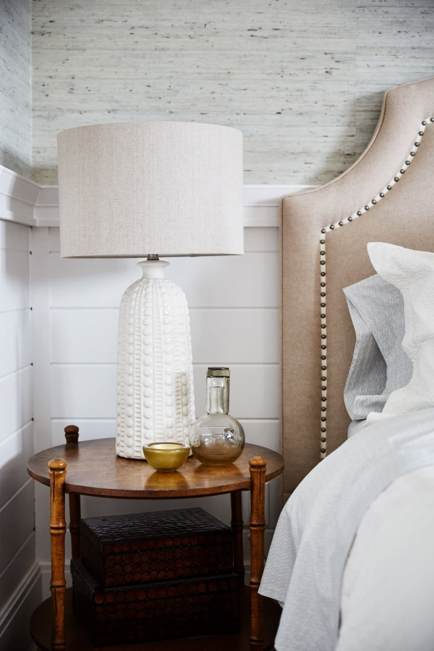 Guest Bedroom with cream lamp on round side table- Sarah off the Grid